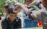 Somro and Kishore from Satla Bheel village playing with water at the newly installed plant system. Photo: Black Box Sounds/ Concern Worldwide.