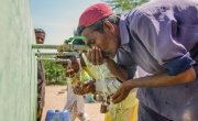 Local men from Satla Bheel village drink clean water from a water plant. Photo: Black Box Sounds / Concern Worldwide.