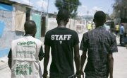 """Pascal Louissant, Concern Haiti, walks through Cité Soleil with members of a local """"Foundation"""". Photo: Concern Worldwide."""