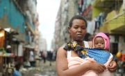 Jacqueline (28) and her daughter Faith (18 months) pictured outside her flat on the street of Pipeline a slum in Nairobi, Kenya. Photo: Jennifer Nolan / Concern Worldwide.