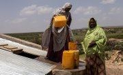 Women collect water in jerry cans.