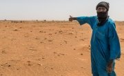 Mahamadou Islam Garmazaye is the Chief of Garmazaye village. He is pointing here to the arid land that has seen very poor harvests for the last five years. Photo: Apsatou Bagaya / Concern Worldwide.