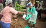 Nurse Mariama Kpakiwa in personal protective equipment is disinfected at Waterloo PHU during Ebola outbreak in Sierra Leone.