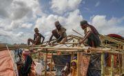 Rohingya men rebuilding their tents before the monsoon arrives.