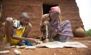 13 year old Abinet, helps his mother, Workinesh Alto, to strip maize cobs in front of the new family home.