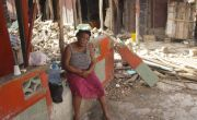 Woman sits on wall surrounded by the ruins of a building destroyed during the earthquake in Haiti