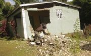 Man sweeps up debris in front of his house, which is collapsing following the earthquake in Haiti