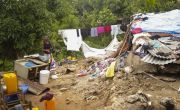 Woman stands beside clothes line full of washing to the left of her destroyed home