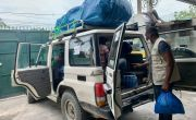 Man takes supplies from the boot of concern jeep vehicle in Haiti