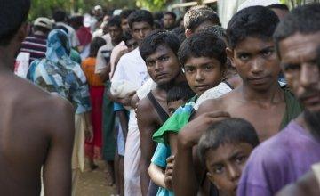 Rohingya men from Myanmar queue at a distribution site at Hakim Para in Cox's Bazar, Bangladesdh. Photo: Kieran McConville / Concern Worldwide.