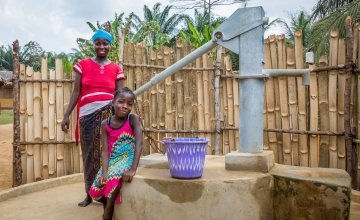 Irene with her daughter Lucy (8) and their new water pump. Photo: Gavin Douglas/Concern Worldwide.
