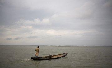 A lone boatman travels accross the Haor flood plains of North East Bangladesh.