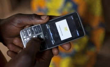 Olivier Irankunda (23) uses his mobile phone at his home in Mabayi, Cibitoke.