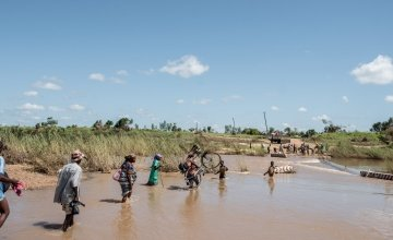 People wade across a river in flood near Nhamatanda, Mozambique. Cyclone Idai has disrupted infrastructure across the country, impacting livelihoods and hampering aid efforts. Photo: Tommy Trenchard / Concern Worldwide.