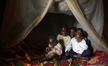 Brothers Salomon (3), David (6), Issa (10) and Selemani (13) in bed with their mosquito net. Photo: Chris de Bode / Concern Worldwide.