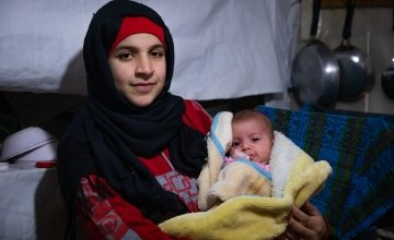 Wafdeh* (20) with her youngest daughter Rajaa* wrapped in a thermal blanket in their makeshift kitchen. Photo: Gavin Douglas/ Concern Worldwide.