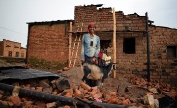 Violette Bukeyeneza outside her dilapidated house with her goat. Photo: Darren Vaughan/Concern.