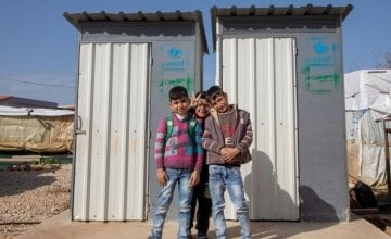 Children from an ITS camp in Northern Lebanon pose beside latrines Concern built.