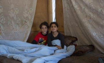 Two Syrian refugee children sit under a duvet