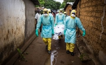A burial team collects a corpse from inside a house in the east of Freetown, Sierra Leone.