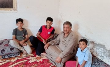 Samar sitting with his brothers and father. Photo: Concern Worldwide.