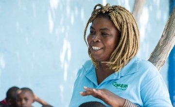 Jasmine listens as Woodson Marcelin tells a story during Children's Parliament activities in Cité Soleil, Port au Prince. Photo: Kieran McConville/ Concern Worldwide.