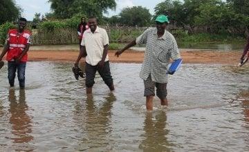 A Concern aid worker walking through flood water in Sudan