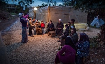 A group of Syrian refugees outside their tents at night.