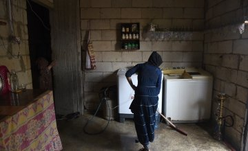 *Sarah cleans the kitchen in her family's home which has been refurbished by Concern in preparation for the winter, in Northern Lebanon Photograph by Mary Turner