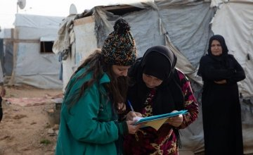 Concern staff working with a Syrian refugee who has received supplies while living in displacement. Photo: Gavin Douglas
