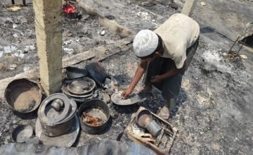 A Rohingya refugee searching through household materials from his home after the fire. Photo: Concern Wordwide.