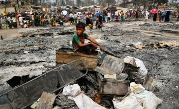 A Rohingya refugee boy sits on a stack of burned material.