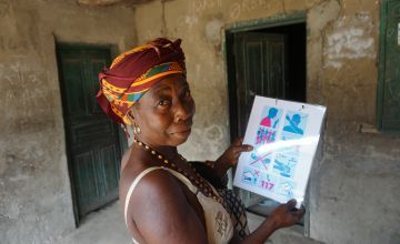 Kumba Tabe Mansaray wife of the Town Chief hanging a Concern Worldwide printed COVID-19 flyer at her residence in Bassaia Village Tonkolili District Sierra Leone Photo: Mohamed Saidu Bah / Concern Worldwide.