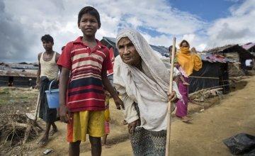 Moburak*, aged eight, leads his grandmother Nur* through Moynadhona refugee camp for Rohingya in Cox's Bazar, Bangladesh. Photo: Kieran McConville/Concern Worldwide.