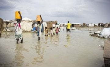 Women walk through contaminated flood waters in a camp in South Sudan.