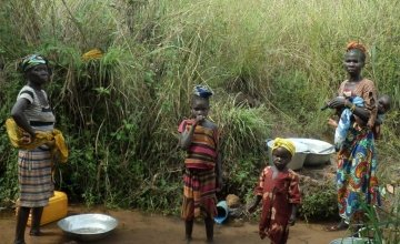 Residents of Bekadili village stand beside a small spring that is used to collect water for drinking, cooking and other household needs. Photo: Crystal Wells/Concern Worldwide.