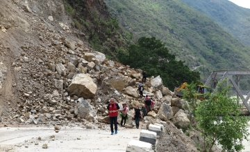 Bulldozers working to re-open a road in Khurkot, Ramechhap  after the recent earthquake in Nepal, with a newly-built bridge in the background. Photo taken by Helvetas.