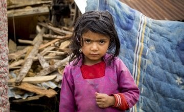 Shiwani Sapkota, in front of the remains of her home in the village of Kukhretar, Kabhrepalanckok district, Nepal. It was destroyed by the 25 April earthquake and she and her family are now homeless. Photo taken by Crystal Wells / Concern Worldwide.