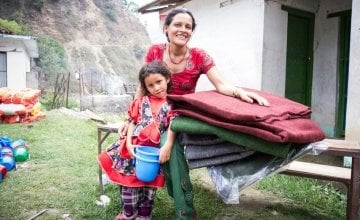 Chameli Darji with her youngest daughter, Apita, with the items they received at a Concern Worldwide and Rural Reconstruction Nepal (RRN) distribution in Talamarang VDC in Sindhupalchok district, Nepal. Photo taken by Crystal Wells / Concern Worldwide.