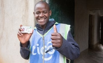 Jean Claude Minani shows off his prized motorcycle driver's licence. He participated in Concern's graduation programme in Rwanda and was able to start his own motorcycle taxi business. Photo: Robin Wyatt / Concern Worldwide, 2015.