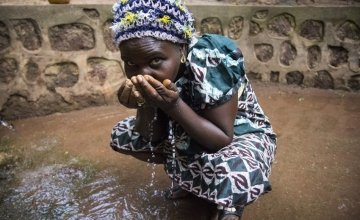 A woman drinks water from one of four new water sources that Concern Worldwide rehabilitated around Dawili, which sits between the towns of Bokoum and Bossembele in Ombella-M'Poko prefecture in southern Central African Republic. Photo taken by Crystal Wells / Concern Worldwide.