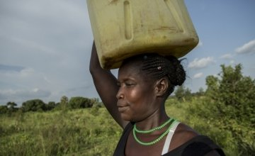 Santina Lalam, a farmer from Agago in Uganda, carries a jerry can on her head to collect water.