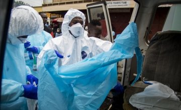 Members of burial team 5 prepare to remove a body from a home in Freetown. Photo taken by Kieran McConville / Concern Worldwide.