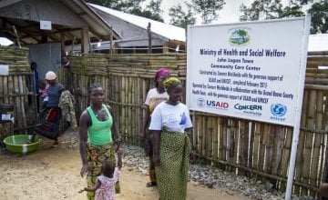 Women leaving the Community Care Centre in John Logan Town, Grand Bassa County, Liberia The centre, built by Concern Worldwide, was designed to treat Ebola patients but has been transformed into a general health centre. Photo taken by Kieran McConville / Concern Worldwide.
