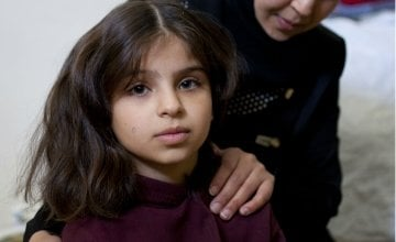 Eight year old Khadiya* with her mother Haya*. Khadiya and her family fled Syria as refugees and now live with three other families in a two-roomed flat in northern Lebanon. Photograph taken by Abbie Trayler-Smith/Panos for Concern Worldwide in December 2015.