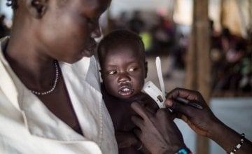 12 month old Gatlit Matiek, pictured with his mother, Nyekliony Bany Gaie. has his upper arm circumference measured at one of the Concern nutrition centers in Bentiu Protection of Civilians (POC) site in Unity State, South Sudan. Photo: Kieran McConville/Concern Worldwide 2016.