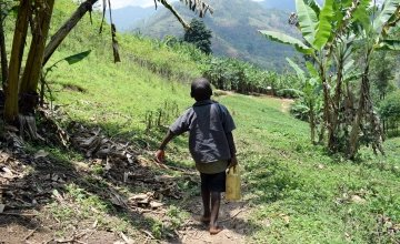 Nishimwe from Burundi makes a two hour journey to school on foot carrying a small container filled with water. Photo: Darren Vaughan/Concern Worldwide.