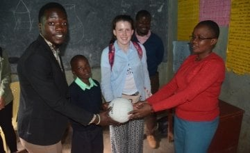 A ball from Michael Darragh McAuley is presented to head teacher Mrs Mary Nabowa and class teacher of class five in Dandora IV prep school. Photo: Francis Mwangi/Concern Worldwide