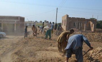 Community members working on building an embankment. Photo: Qurban Ali/ Concernworldwide.