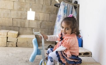 Two and a half year old Oula* plays with her favourite toy, outside her newly rehabilitated home in northern Lebanon. Photo: Chantale Fahmi/Concern Worldwide 2017.